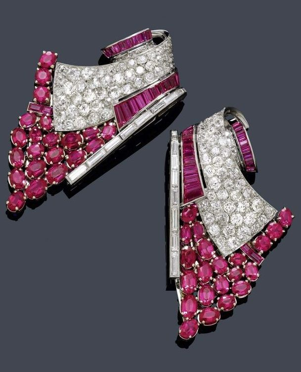 "AN ART DECO DIAMOND DOUBLE CLIP, France, ca. 1935. Geometrically shaped double clip brooch with stylised, scrolled band motifs, each set throughout with 21 synthetic oval rubies, graduated, and with numerous baguette-cut rubies, and each additionally decorated with 10 baguette-cut and 57 old European-cut diamonds, mounted in platinum and white gold. Maker's mark ""CR"". #ArtDeco #DoubleClip"