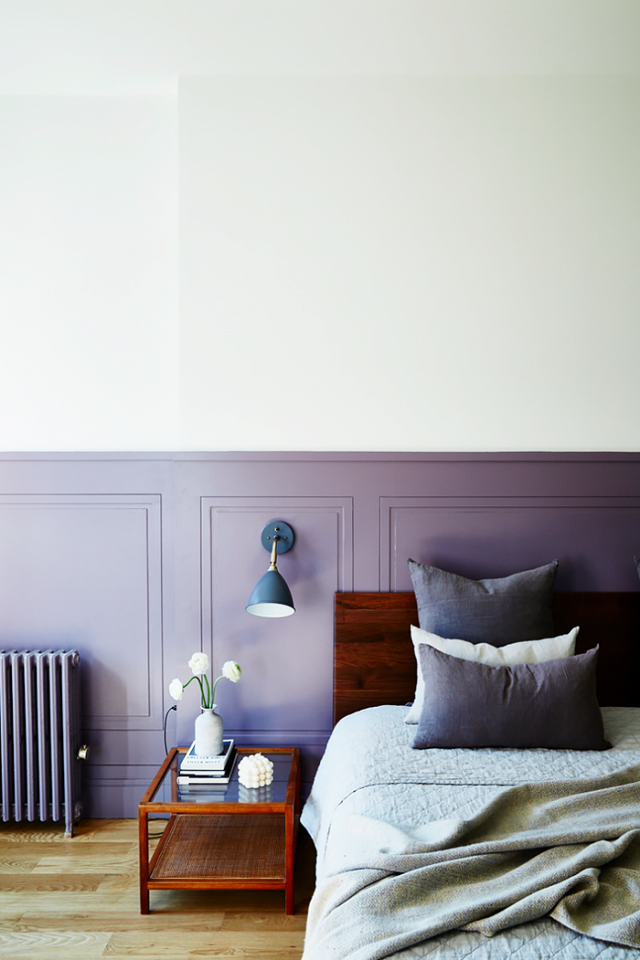 Bedroom with a two-tone painted wall and a simple wood headboard