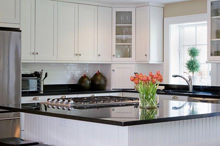 Große weiße Küche mit Geräten aus rostfreiem Stahl und große Insel ...