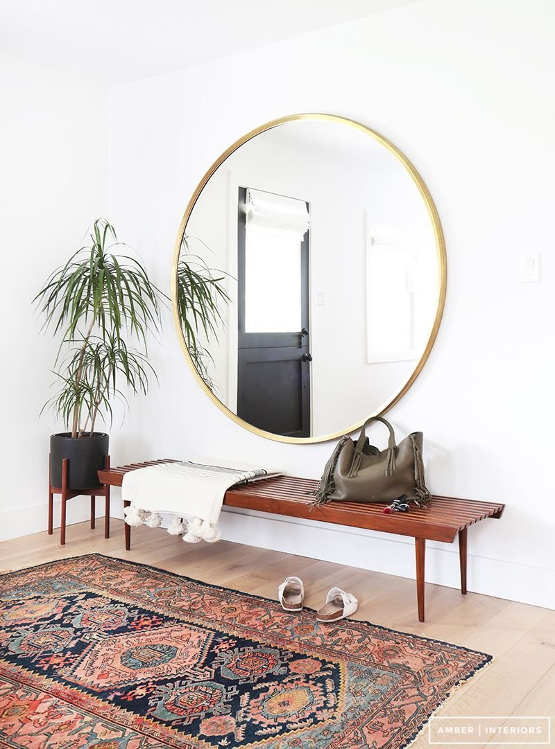 Midcentury modern meets bohemian entryway with a slatted bench vintage persian rug and oversized gold round mirror