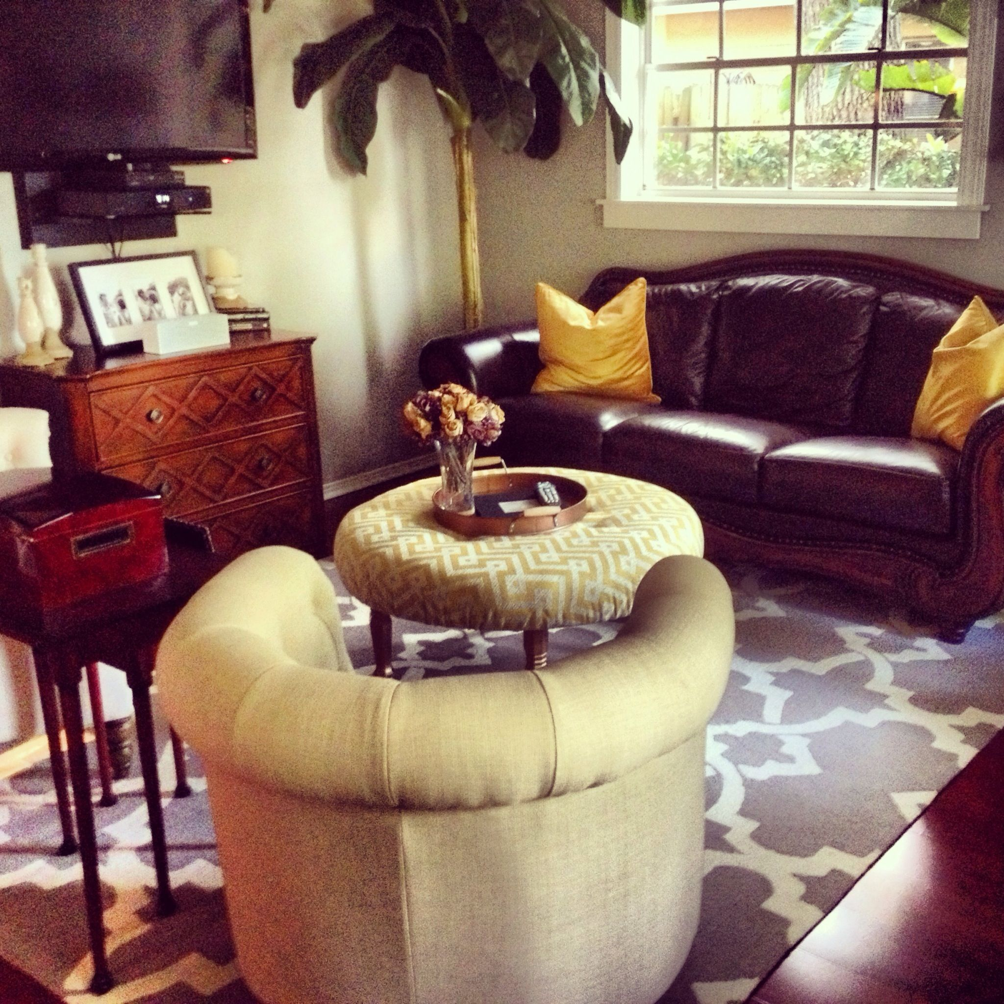 Gray Trellis Rug, Yellow Chevron Ottoman, And Brown Leather Couch