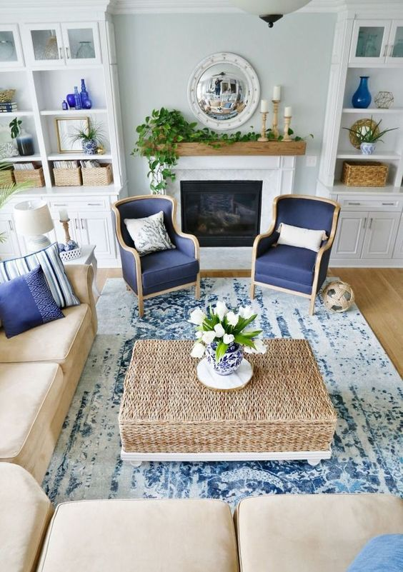 a traditional coastal living room with a tan and navy color scheme, rattan, leather and a mantel with greenery #coastallivingrooms