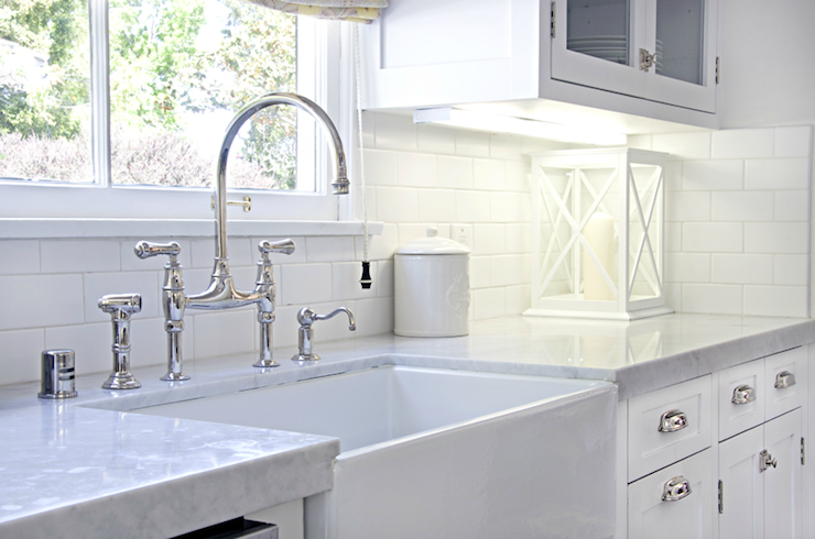 Galley kitchen   farmer sink with perrin  rowe bridge faucet white glass front cabinets also