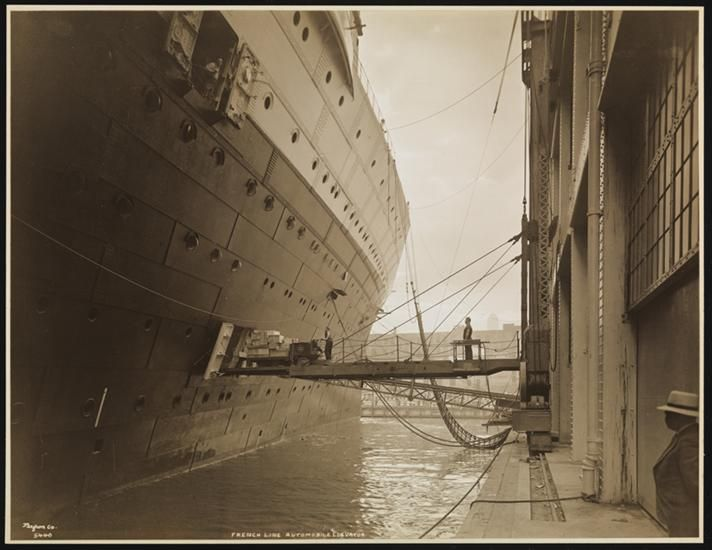 """French Line, S.S. """"Normandie"""", Pier #88 N.R., Truck of Boxes on Elevator Going Aboard Steamer--View from Inside of Pier."""
