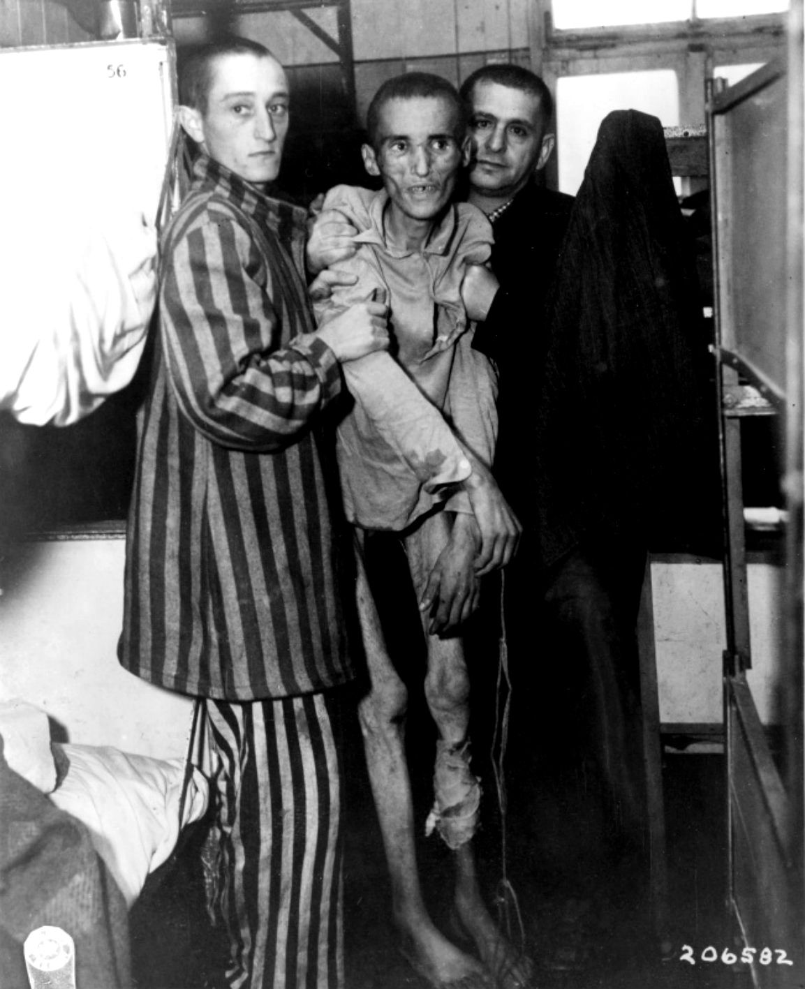 A 23-year-old Czech inmate at Flossenbürg concentration camp, recently liberated by the elements U.S. Army's 2d Stryker Cavalry Regiment, 90th Infantry Division and 97th Infantry Division, is held aloft by fellow internees, suffering from severe...