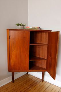 Danish Modern Corner Cabinet Clad In Teak In Excellent Vintage Condition.  This Cabinet Has Beautiful Brass Skeleton Key Holes That Lock The Cabinet.