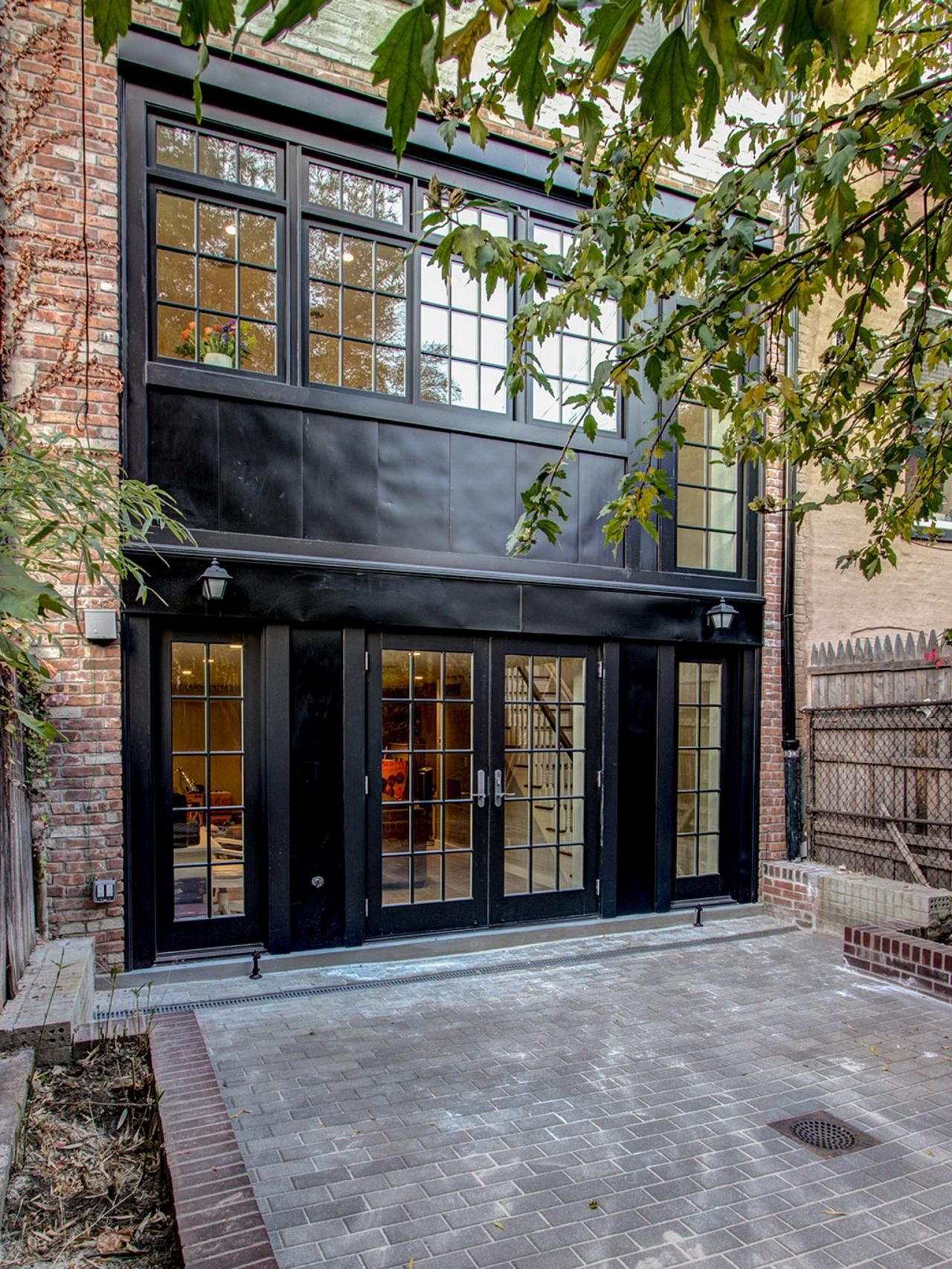The rear facade of this brooklyn townhouse is painted all - Houses with black windows ...