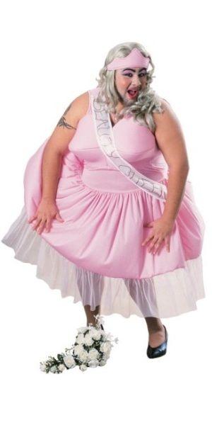 Kauneus Kuningatar. Mekko täytetyillä rinnoilla, tiara ja olkanauha.
