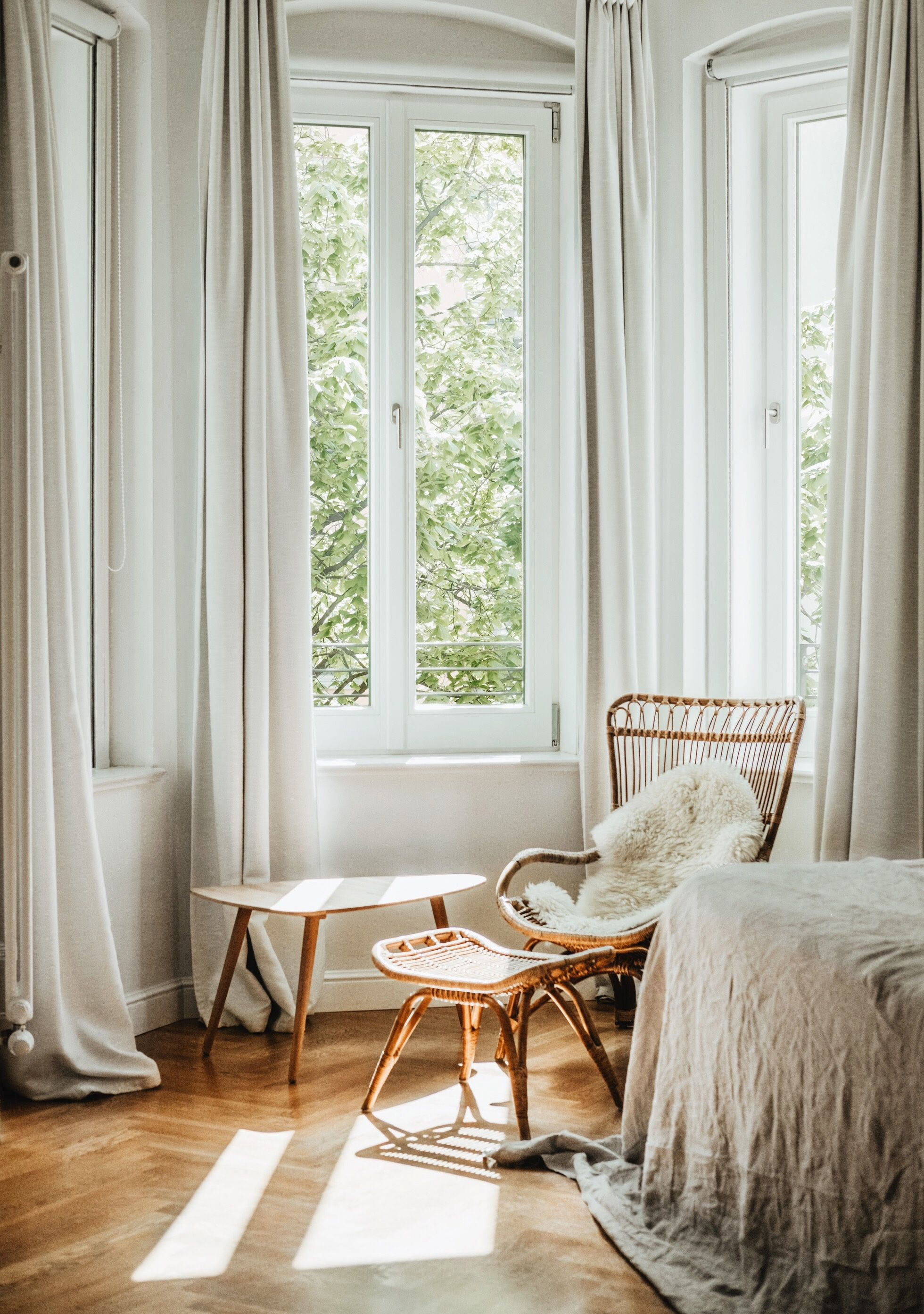 Lovely white and natural bedroom with a rattain chair nect to the ...