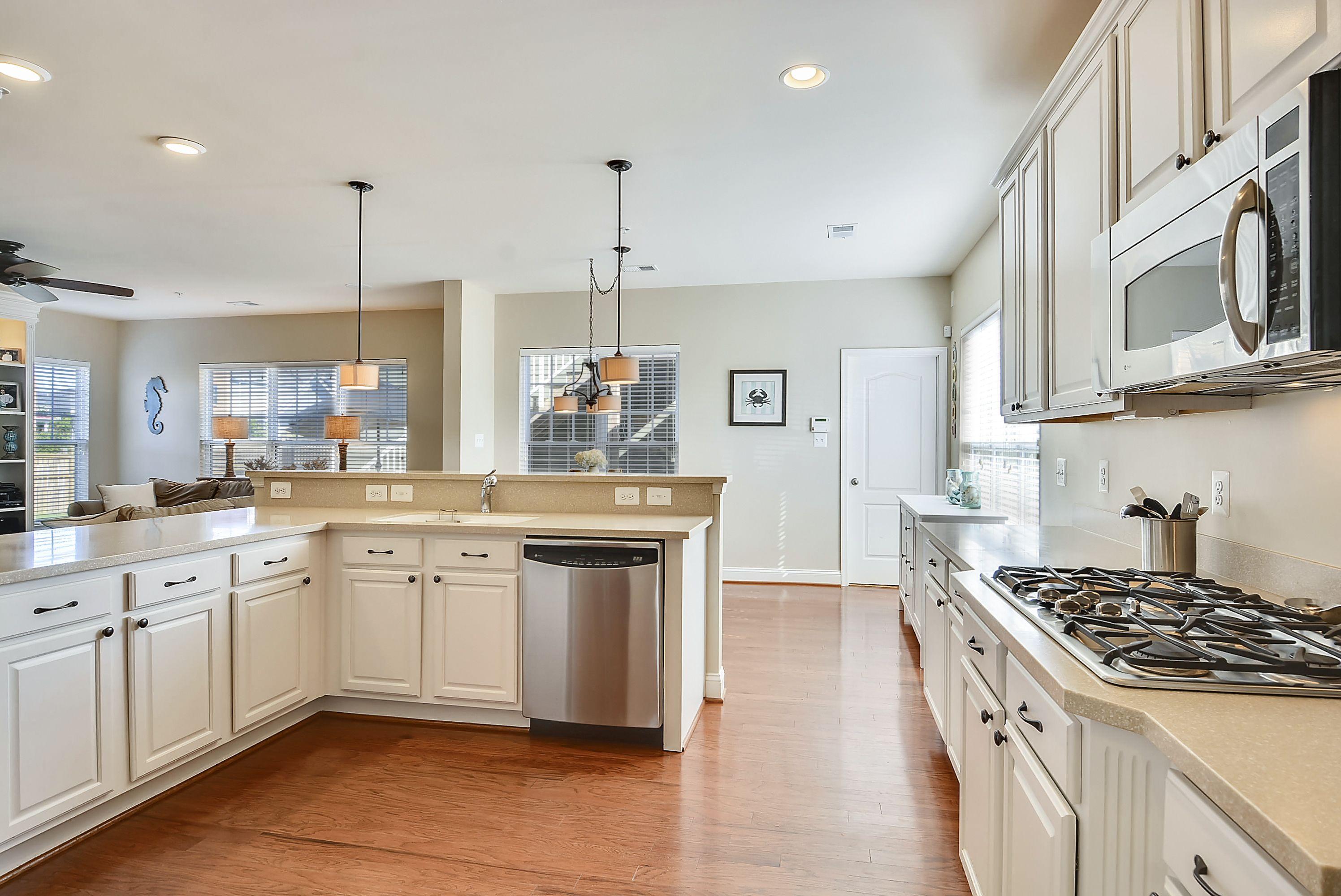 White cabinets, cream silestone countertops, hardwood ...