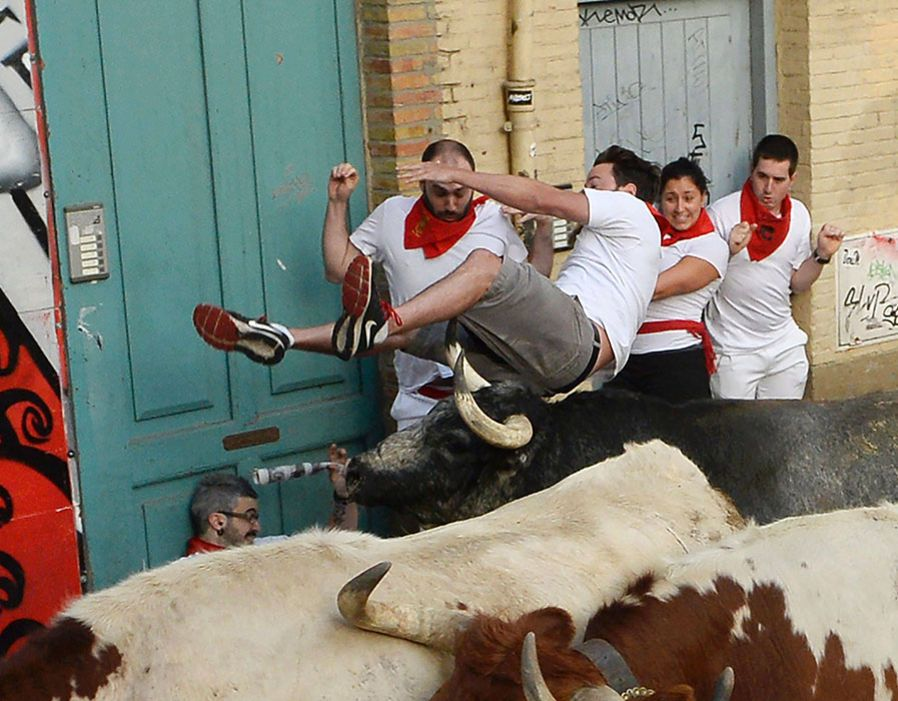 21 / 31 A participant is tossed by a Cebada Gago fighting bull on the first day of the San Fermin bull run festival in Pamplona..