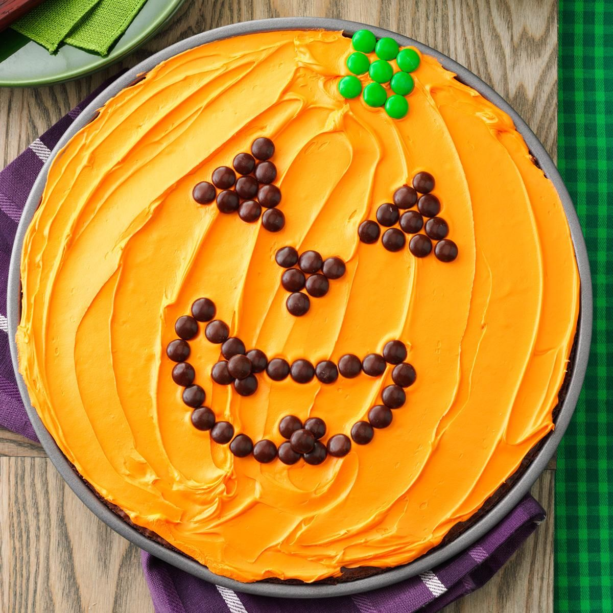 Great Pumpkin Brownie Recipe -Our kids beg for these big brownies every year. I just bake brownie batter in a pizza pan, spread with orange-tinted frosting and let the kids design a pumpkin stem and jack-o'-lantern face using candy. —Darla Wester, Meriden, Iowa