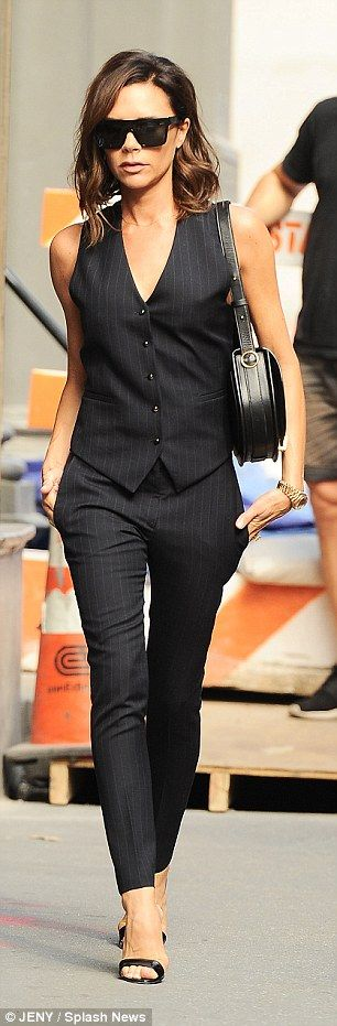 Strutting her stuff: She paired the figure-hugging trousers with a navy waistcoat that cinched in her tiny midriff