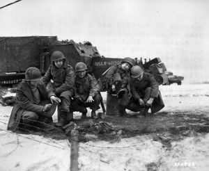 On the outskirts of Bastogne, paratroopers of the 101st Airborne Division and tankers of the 6th Armored Division gather around a fire five days after the surrounded city had been relieved. Some of the men are pulling their newly warmed overshoes over their boots.