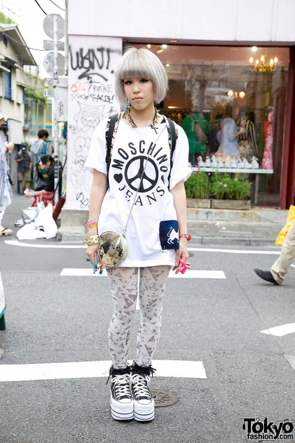 This is Miho, a 21-year old Japanese student. Miho may – or may not – be twins with our previous street snap Maho. Miho and Maho were hanging out together when we spotted them in Harajuku, and they gave us the same family name and age. Miho is wearing a a Moschino top with Nadia shorts (hard to see in the photos), cute tights (I've seen this pattern before, maybe at Sister in Shibuya?), ruffle socks, and platform Converse Chuck Taylor All Stars (also from Nadia Harajuku). Accessories – some…