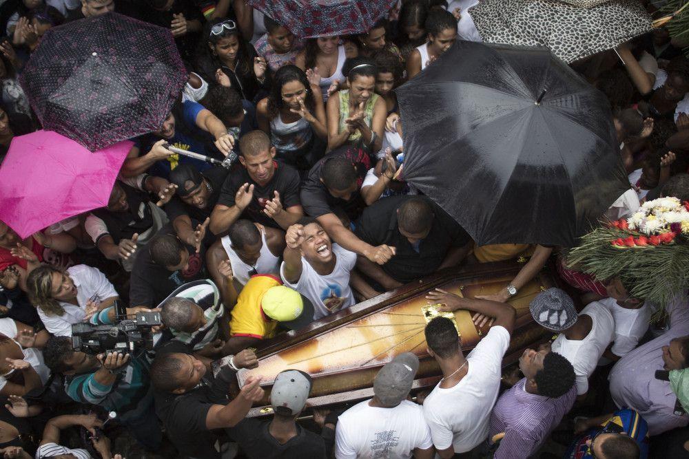 En esta foto de archivo del 24 de abril 2014, los familiares y amigos de Douglas Rafael da Silva Pereira lloran alrededor del ataúd, ya que lo entierran en Río de Janeiro, Brasil. Una protesta siguió el entierro de Silva Pereira, cuya muerte a tiros provocado enfrentamientos entre la policía y los residentes. (Foto por Felipe Dana / AP Photo)
