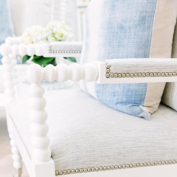 A blue pillow sits atop a white spindle accent chair with