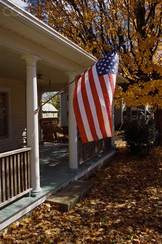 American Flag Hanging From Front Porch Of Home Outdoor Flags