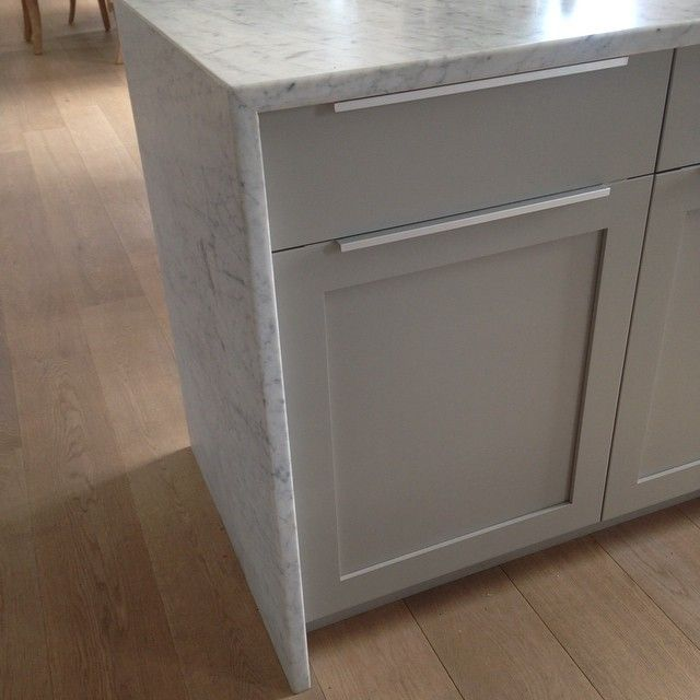 Waterfall countertop detail with white carrera and painted gray cabinets #waterfallcountertop