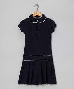 Little ladies will look perfectly polished in this polo dress. Buttons in front makes it easy to slip on, while pleats and bright piping add tasteful flair to this classic getup.