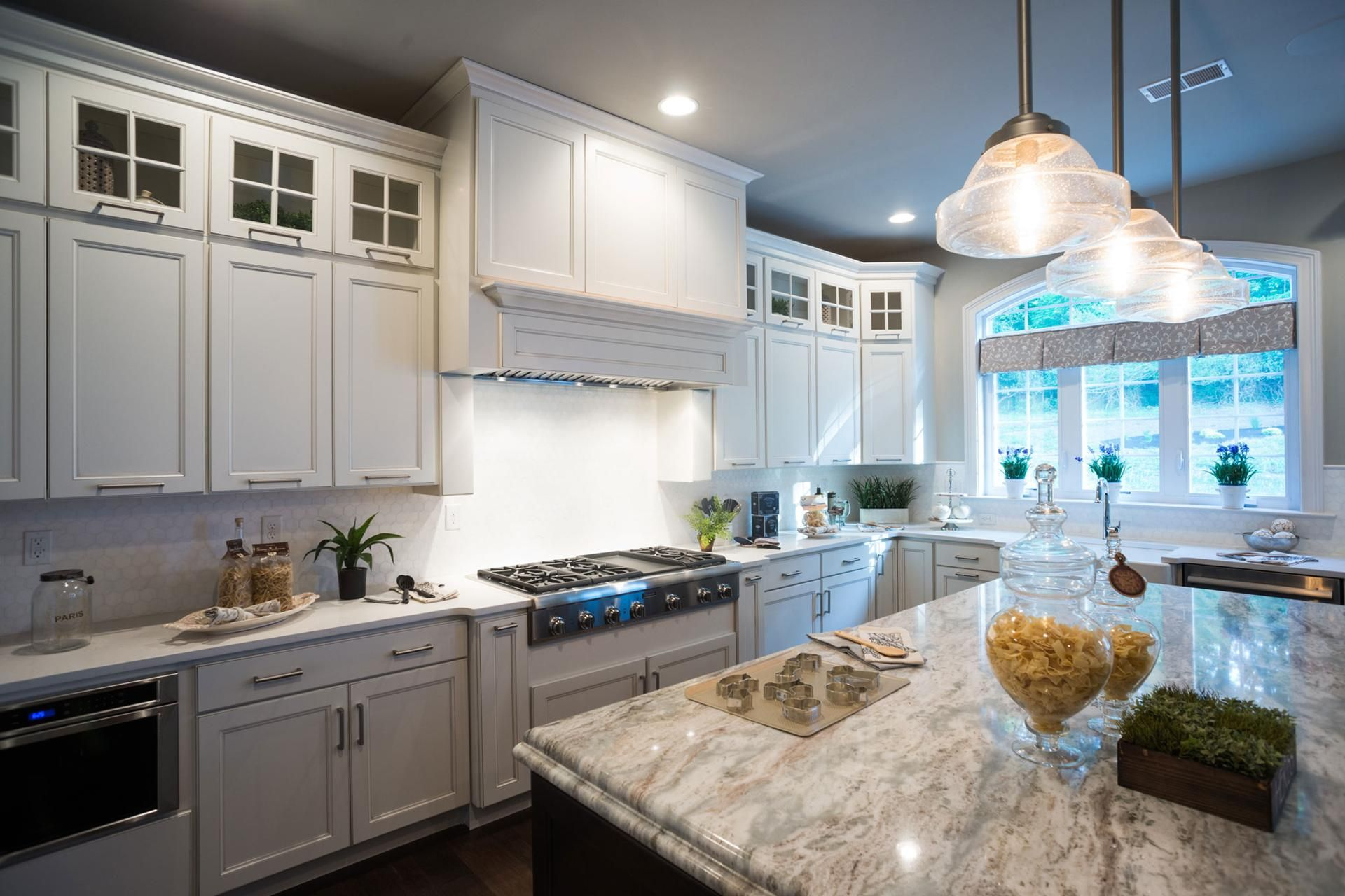 A Top Row Of Glass Fronted Cabinets Are A Distinctive Touch