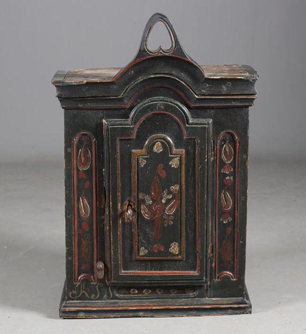 Lite dekorert og utskåret hengeskap, 1700 tallet. H: 64 cm. B: 42 cm. Noe restaurert. Prisantydning: ( 20000 - ).  The top is very unusual.