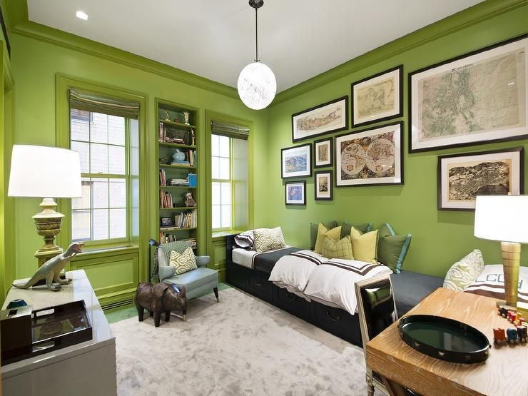 Fantastic boy's bedroom features walls painted bright green lined with a collection of framed maps over a long black daybed with storage drawers dressed in white and brown hotel duvet and shams along with a gray flannel blanket and green pillows with turquoise trim.