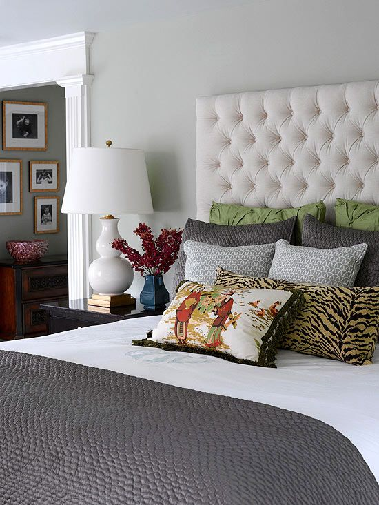 Consider Comfort:   Here, silvery gray walls and a velvet-upholstered headboard inspire this marvelous medley of pictorial, animal print, quilted, and patterned pillows showcased on top of a white sheet, turned over a charcoal gray coverlet. Asparagus green touches energize the monochromatic scheme.
