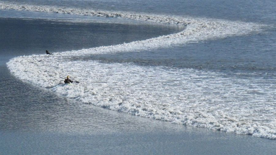 Kayakers ride tidal bore wave as it surges into Alaska's Turnagain Arm