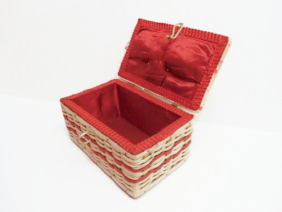 Sweet! Probably dates to the 1970s or 1960s. Cute plastic wicker sewing box with padded fabric top, lined with red satin. Measures about 7 1/2 long, 5 wide, and 4 tall (not including handle). Condition: The plastic wrapping has loosened from the handle; there is slight discoloration/staining to the red satin inner base, nails on outer base show rust/discoloration; and there is an adhesive label (not from this sewing box) which somehow got attached to the base. Still very shabby chic cute…