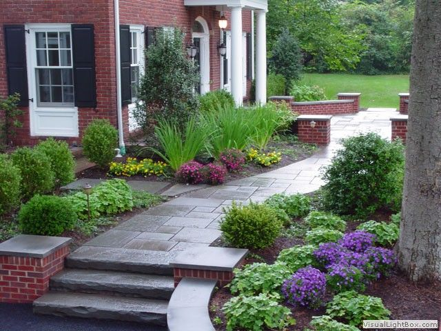 Curved Brick Retaining Wall With Front Yard Plantings Stone Slab Steps Front Walkway Landscaping Walkway Landscaping Landscaping Entryway