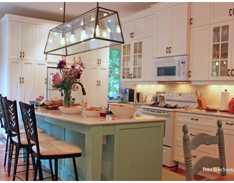 lighting over island - cabinets all the way to the ceiling and different colored island.