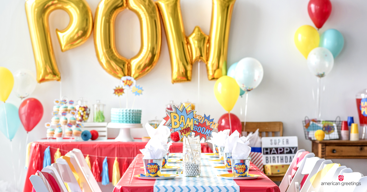 Features A Birthday Cake On Superhero Themed Table Complete With Centerpiece Drink Dispenser Party Favors And Balloons