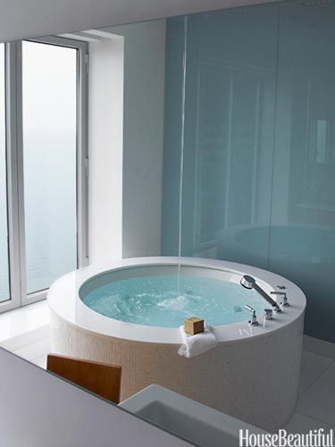 """Created to be the """"ultimate spa experience,"""" this enviable bathroom offers a breathtaking view of downtown Chicago from the circular tub."""