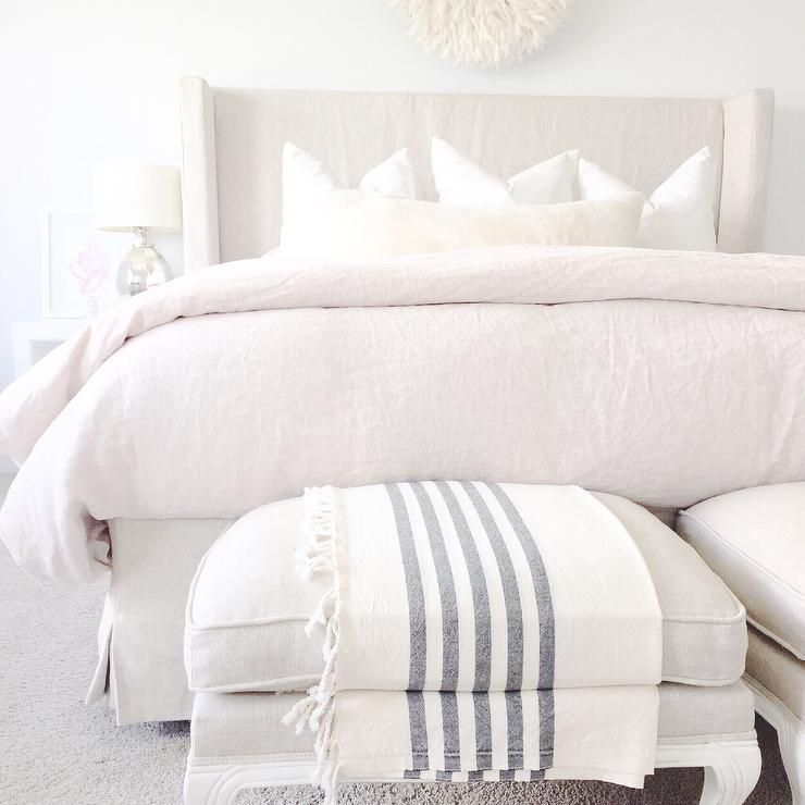 Monochromatic bedroom features a linen slipcovered wingback bed dressed in linen bedding Master bedroom bed linens
