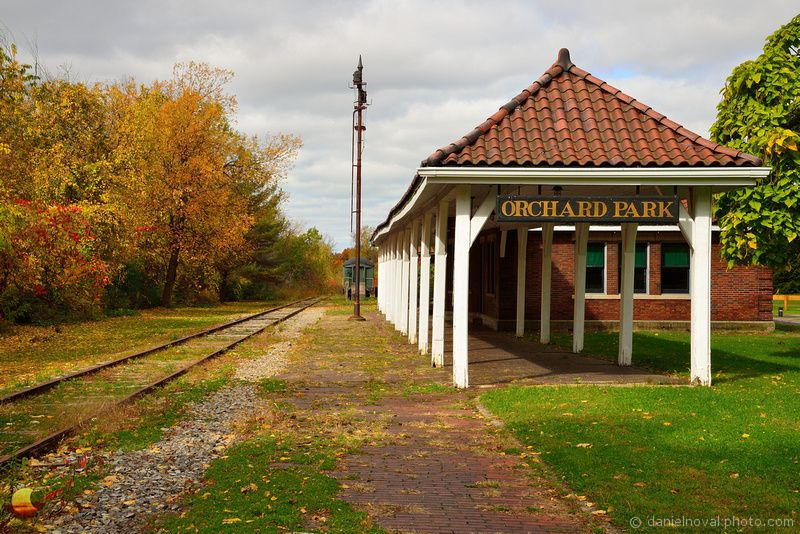Orchard Park Train Depot in the Fall: The railroading days of the Orchard Park Train Depot are gone by but the depot looks great and serves as a reminder of the town's and region's history. On this day, I was lucky enough to capture its look under cloudy skies that helped bring out the colors of the surrounding foliage as well as provide a nice neutral backdrop further intensifying the boldness of those colors. I like to come here often to explore the look through ...