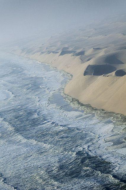 Waves of the Atlantic breaking against the sand cliffs of Namib desert, Namibia (by elosoenpersona).