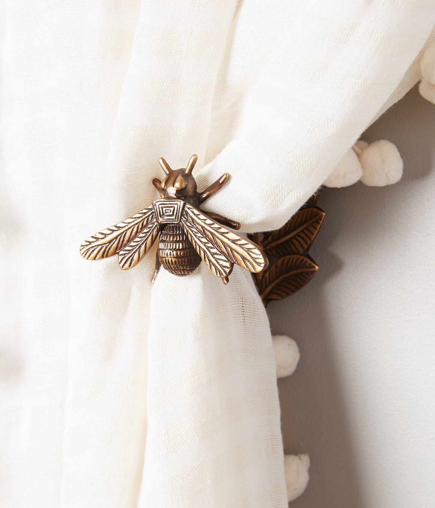 Queen bee curtain tie backs from Anthropologie. How cute would these be on  nursery curtains?