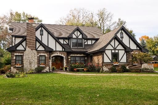 Tudor style home based in the 1920's based on old English, stone, stucco, and wood, features tall chimney and steep roof.
