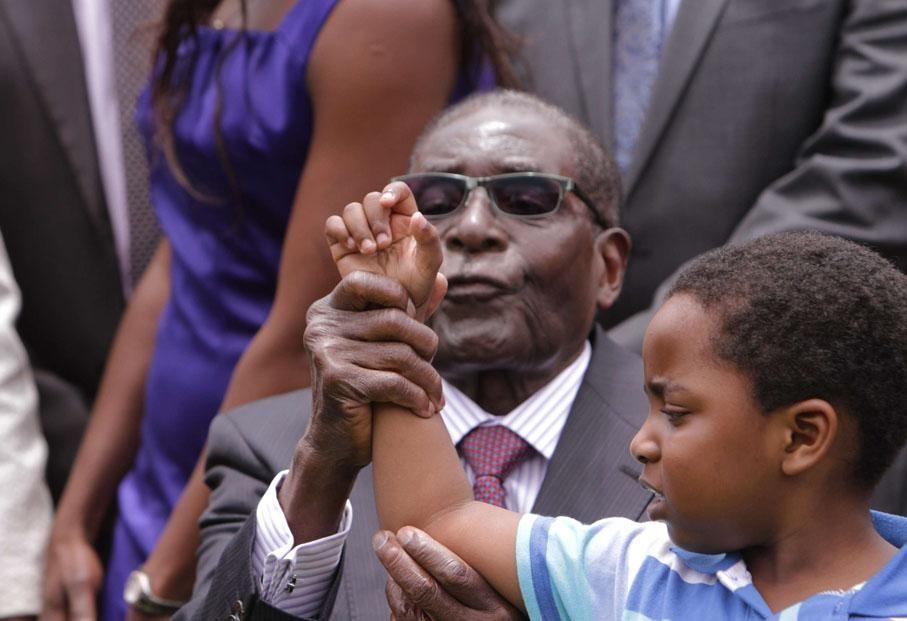 Le président zimbabwéen Robert Mugabe tente de faire chanter le petit-fils d'un de ses vice-présidents lors d'une cérémonie à Harare (Zimbabwe), le 12 décembre 2014.