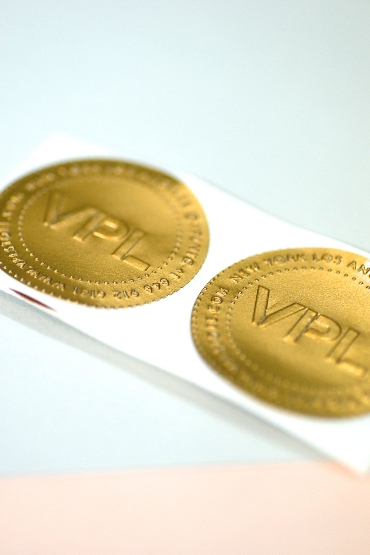 Our embossed logo in gold embossed to 2 dot sticker in metallic