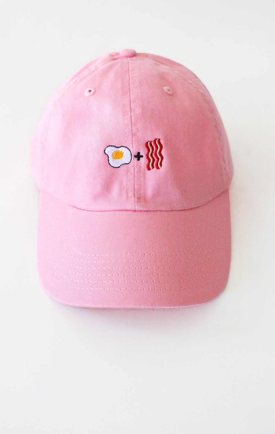 b38efd577 Description Details: Six panel cap in pink with 'Egg + Bacon' embroidery &  adjustable back with tri-glide buckle. Brand: NYCT Clothing. 100% Chino  Twill.