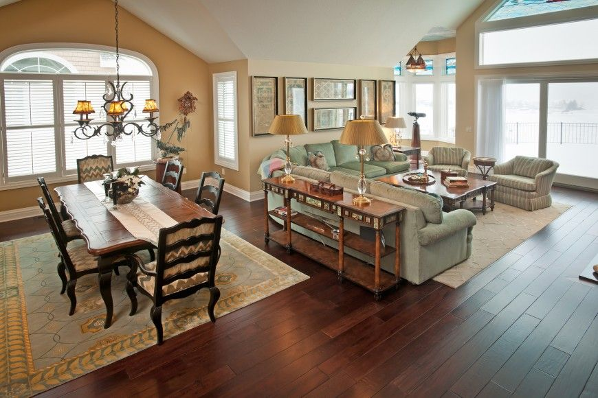 Between The Kitchen And Living Room Areas A Grand Dining Table Sits Below An Ornate