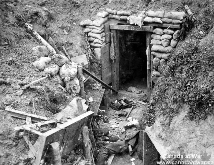 Demolished German Trench - The body of a dead German soldier lies near the entrance to his dugout. While the entrance is intact, the sides of the trench have collapsed. Common items such as an entrenching tool, a water bottle, and ammunition pouches lie scattered on the ground. The numbers on the dugout frame may refer to the unit designation or to the dugout's number in relation to a trench map. CWM 19920044-195