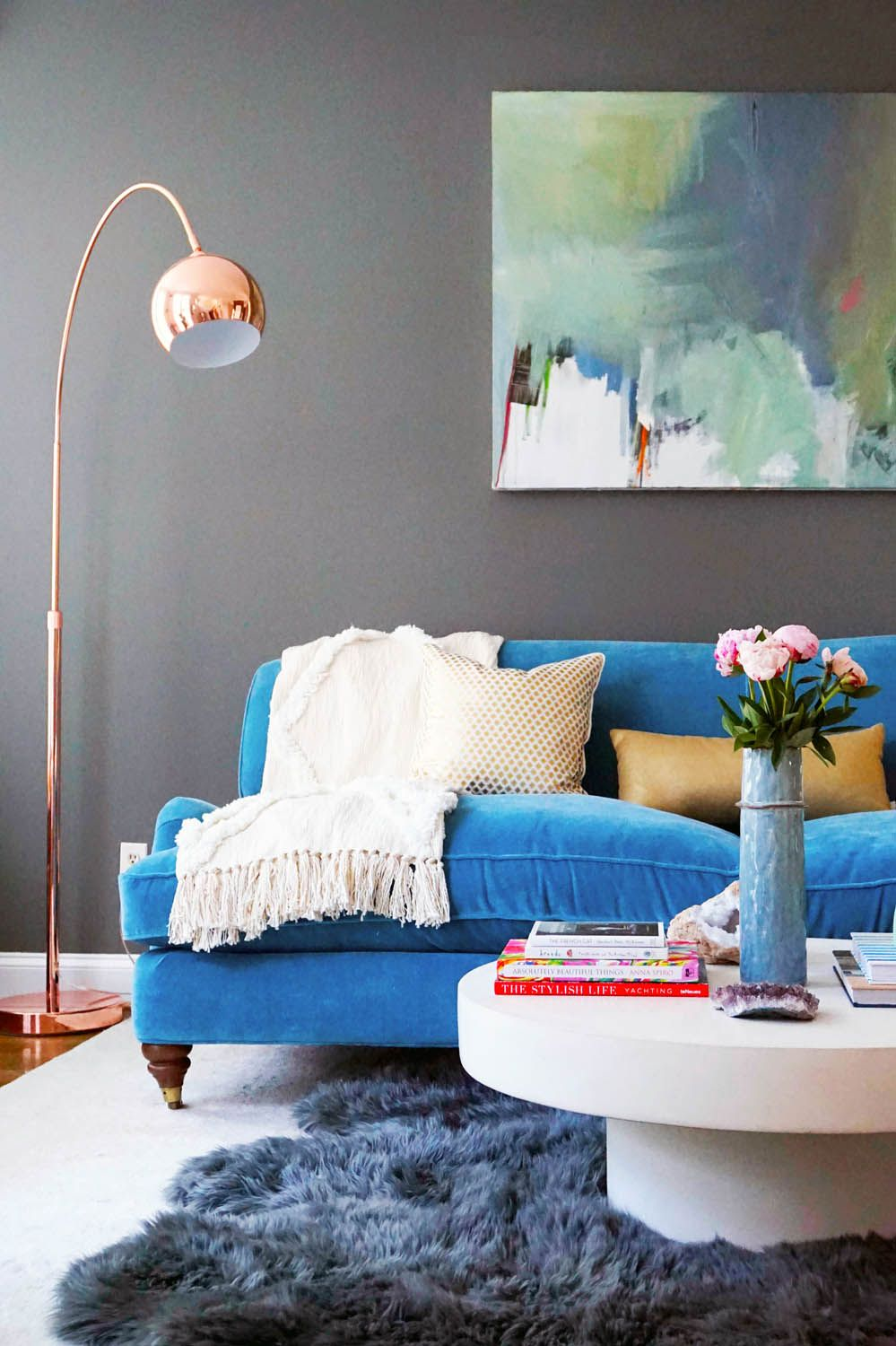 Blue velvet sofa with grey walls and colorful abstract art a