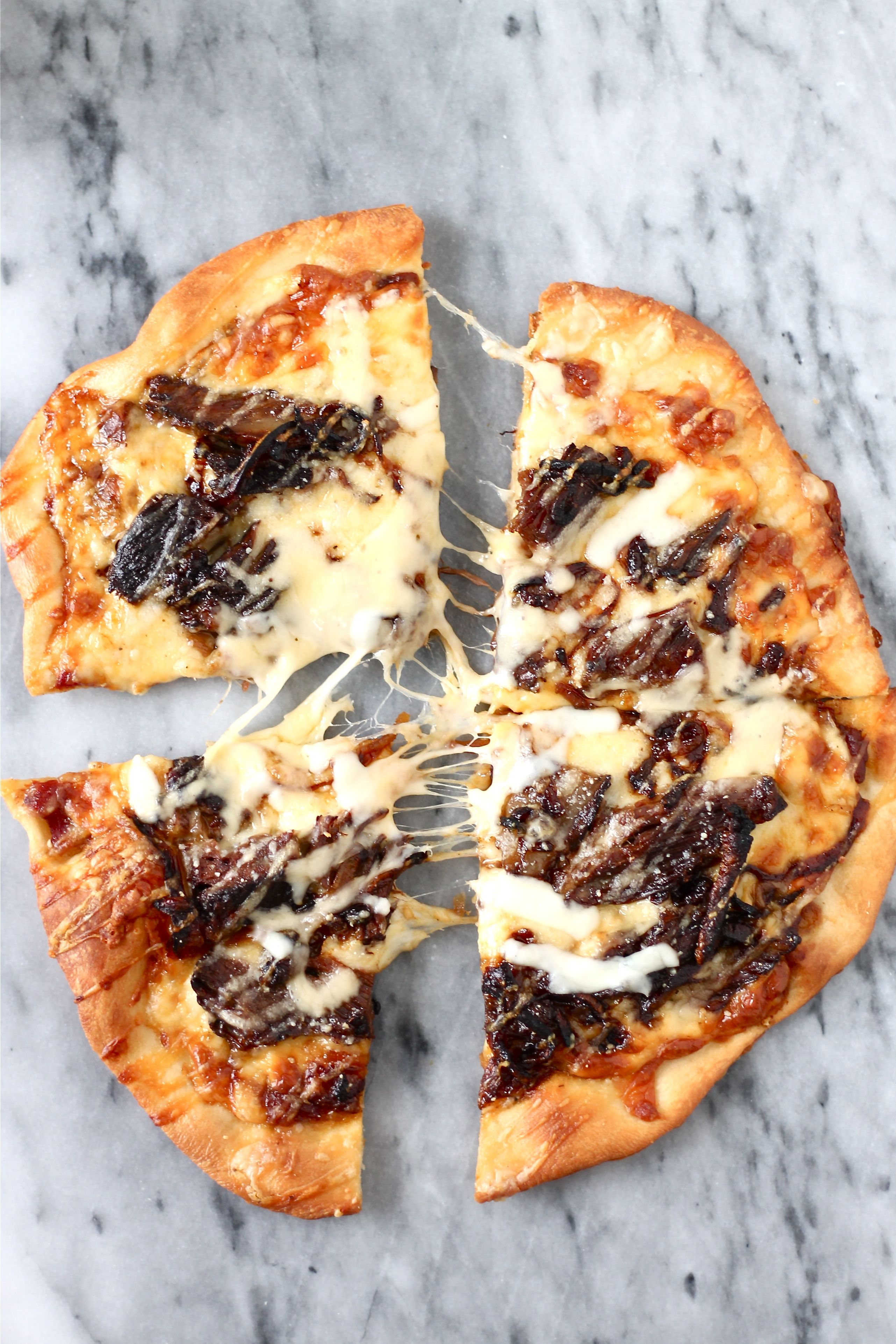 Short rib pizza with mozzarella, caramelized onions, and a smoked gouda cream sauce.