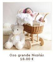 foto monisima de bebe en un carrito con un oso de peluche y un gorrito de crochet