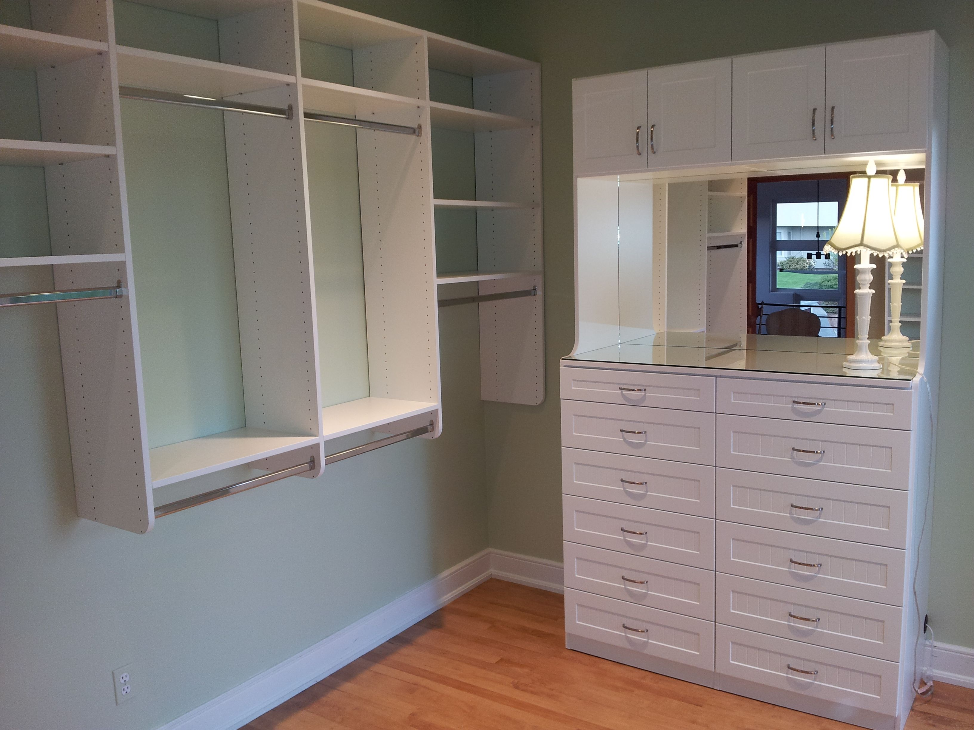 Change that small spare bedroom into a beautiful walk in closet. White bead board doors and drawers with a glass top and a mirror for depth.