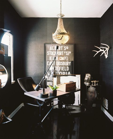 A crystal chandelier and black grass-cloth wallpaper in an office