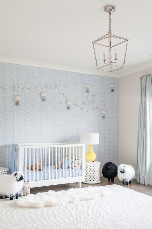 Gorgeous blue and white nursery features a white c...